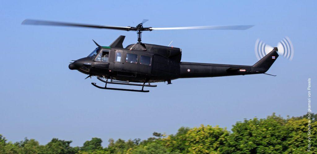 Ein Bell-UH1 Helikopter im Flug über Wald
