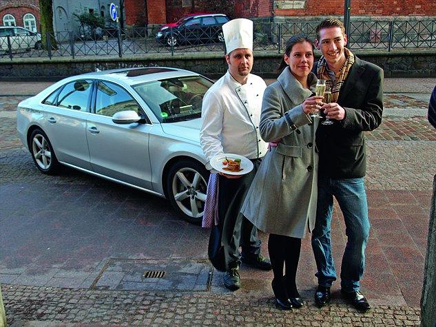Zwei Gäste stoßen an und ein Koch