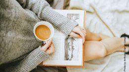 Frau liest ein Buch mit einer Tasse Kaffee