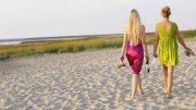 Zwei Frauen mit Sektflasche am Nordseestrand