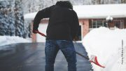 Mann räumt den Schnee einer Ausfahrt weg