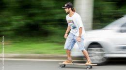Junger Mann in Shorts auf einem Longboard