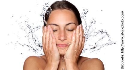 Frau spritzt sich Wasser ins Gesicht