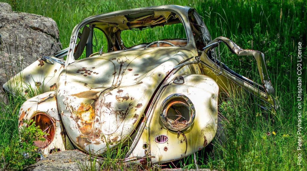 Ein VW Käfer als Schrottauto auf der Wiese