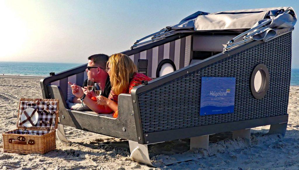 Schlafstrandkorb mit Paar am Strand