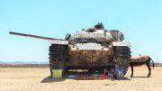 Mittagspause in der Wüste unter einem Panzer