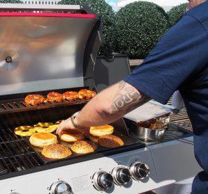 Mann am Grill grillt Burger