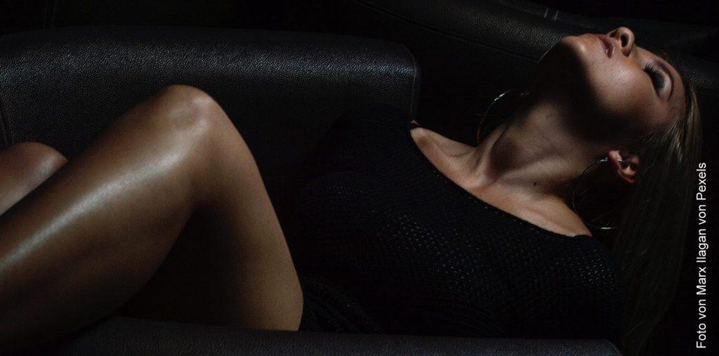 Eine Frau liegt im dunklen auf deinem Ledersofa