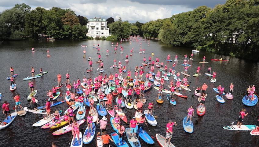 SUP Paddler bei einer Hamburg wird pink Aktion auf der Alster
