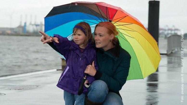 Mutter und Tochter unter einem Regenschirm am Hamburger Hafen