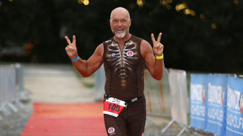 Läufer läuft beim Triathlon durchs Ziel