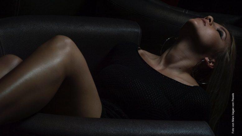 Frau liegt auf einem Ledersofa