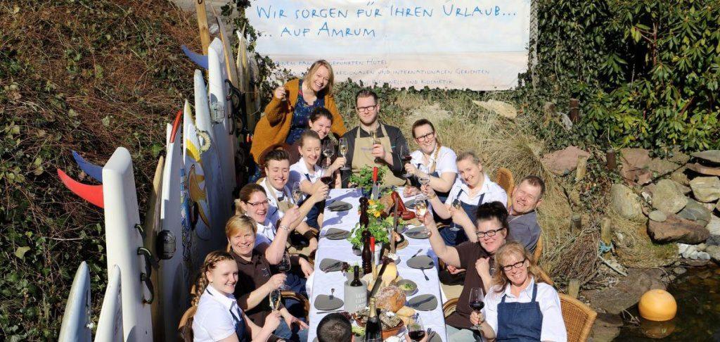 Das Team vom Seeblicker auf Amrum sitzt an einer Festtafel im Freien