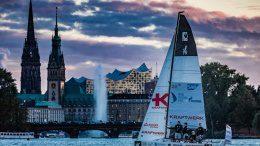 Segelboot auf der Außenalster in der Abenddämmerung mit Hamburger Rathaus und Elbphilharmonie