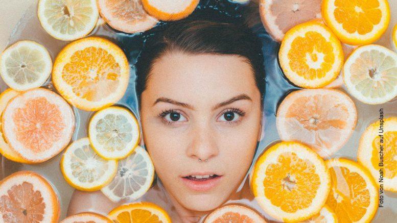 Bei der Hautpflege - Frau in der Wanne mit Orangenscheiben