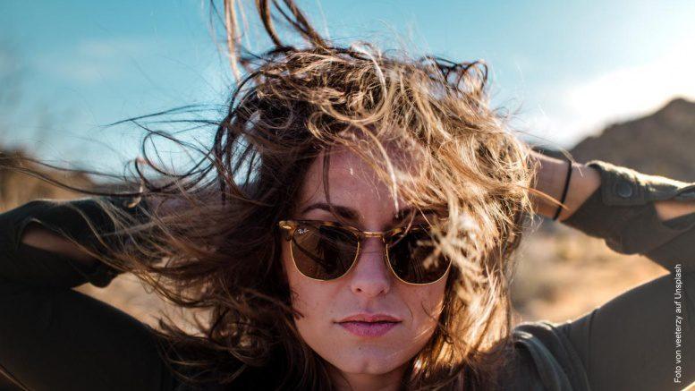 Blonde Frau mit Sonnenbrille und Wind im Haar