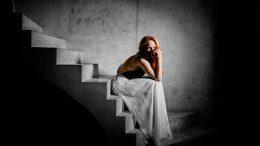 Kat Wulff sitzt im weißen Kleid auf einer Treppe