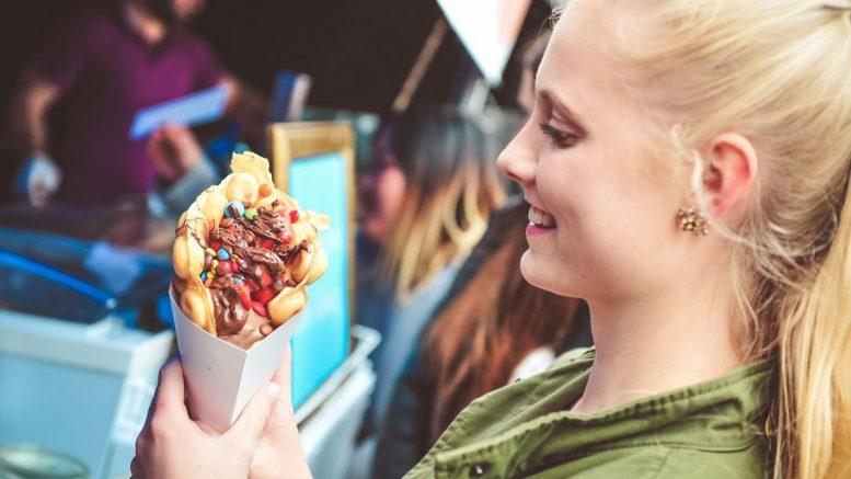 Eine junge Frau isst Streetfood