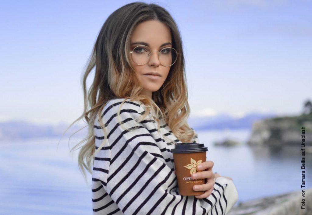 Frau mit Kaffeebecher am Wasser
