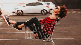 Frau im Einkaufswagen auf einem Parkplatz