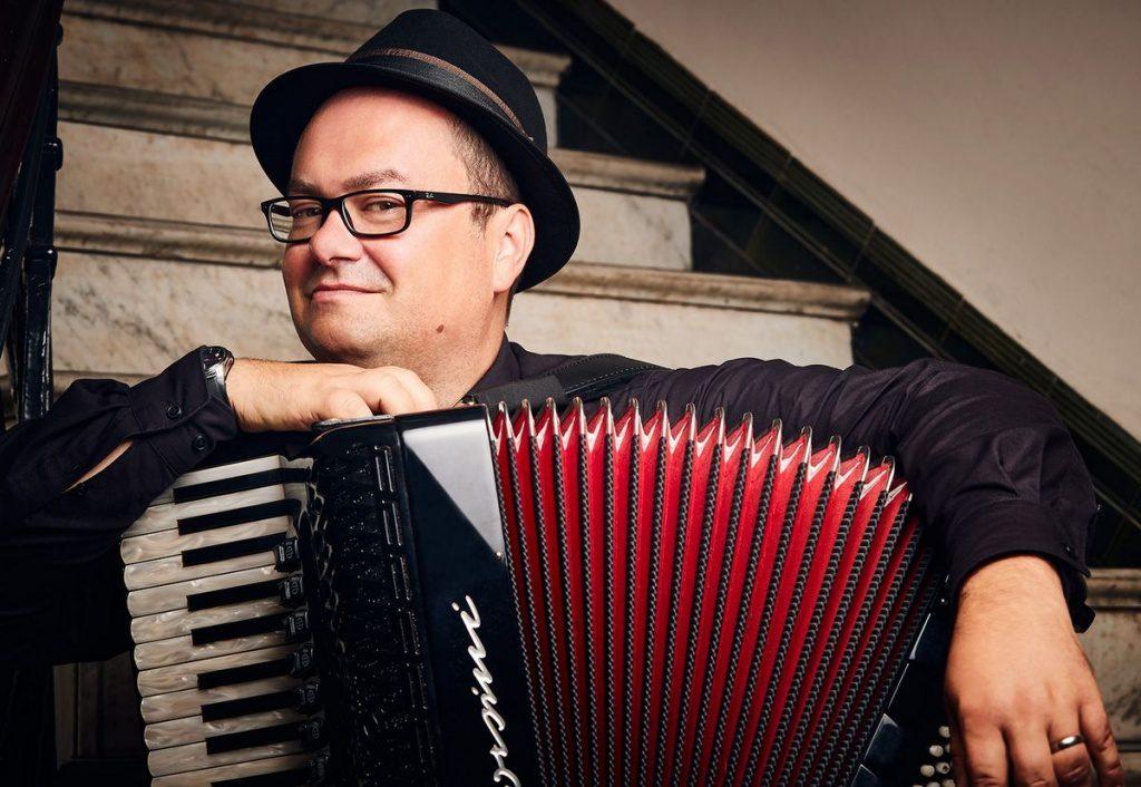 Der Akkordeonmusiker Frank Grischek auf einer Treppe mit Akkordeon