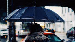 Frau mit Regenschirm unter einer Brücke