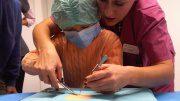 Ein Kind schneidet mit dem Skapell zusammen mit einer Ärztin