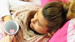 Frau liegt krank mit Tee im Bett