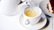 Aus einer Teekanne wird Tee in eine Tasse eingeschenkt
