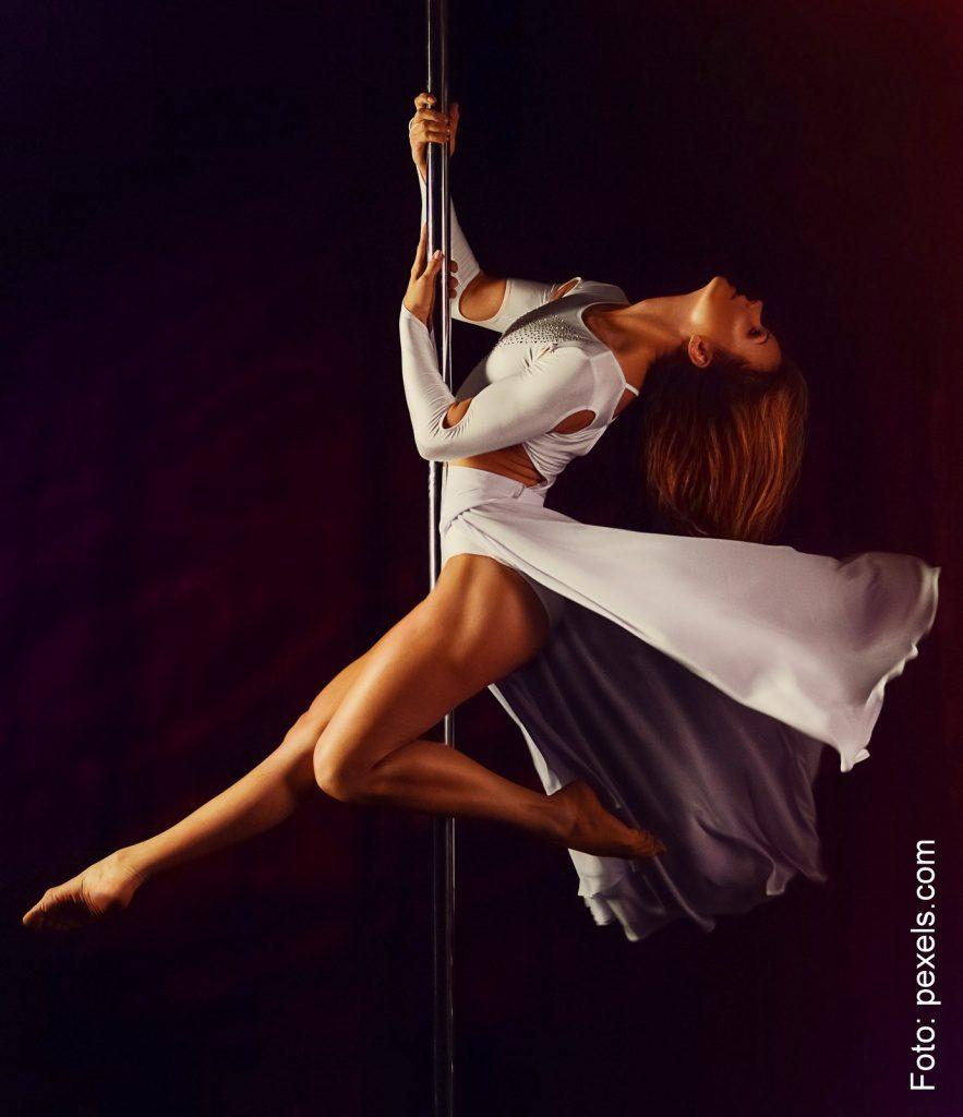 Frau praktiziert Pole Dance im weissen Kleid