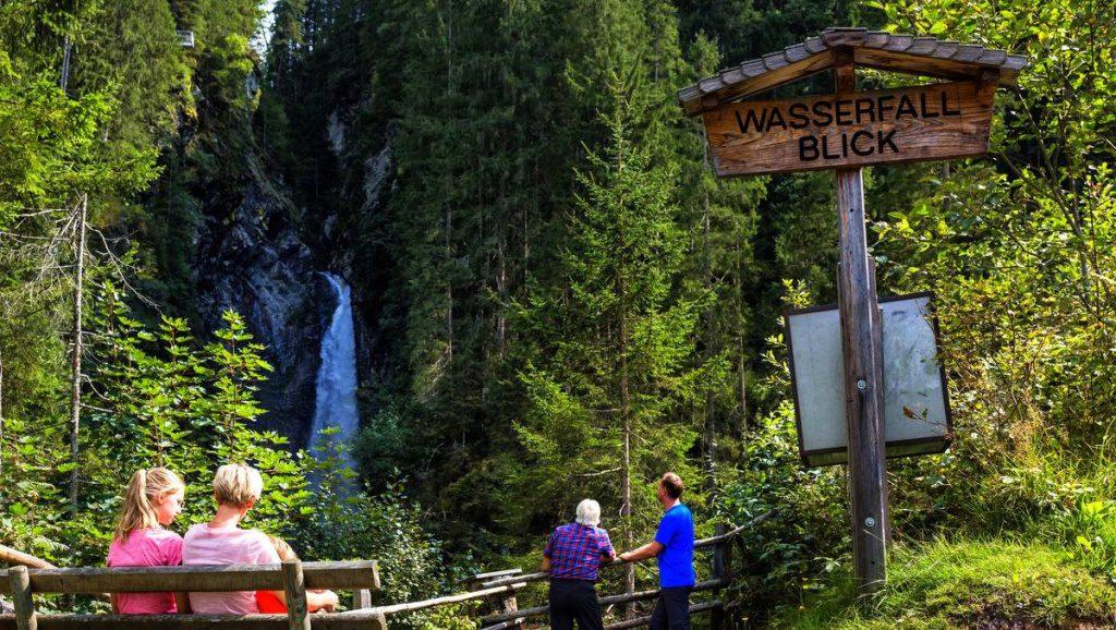 Familie macht eine Pause beim Wasserfallblick