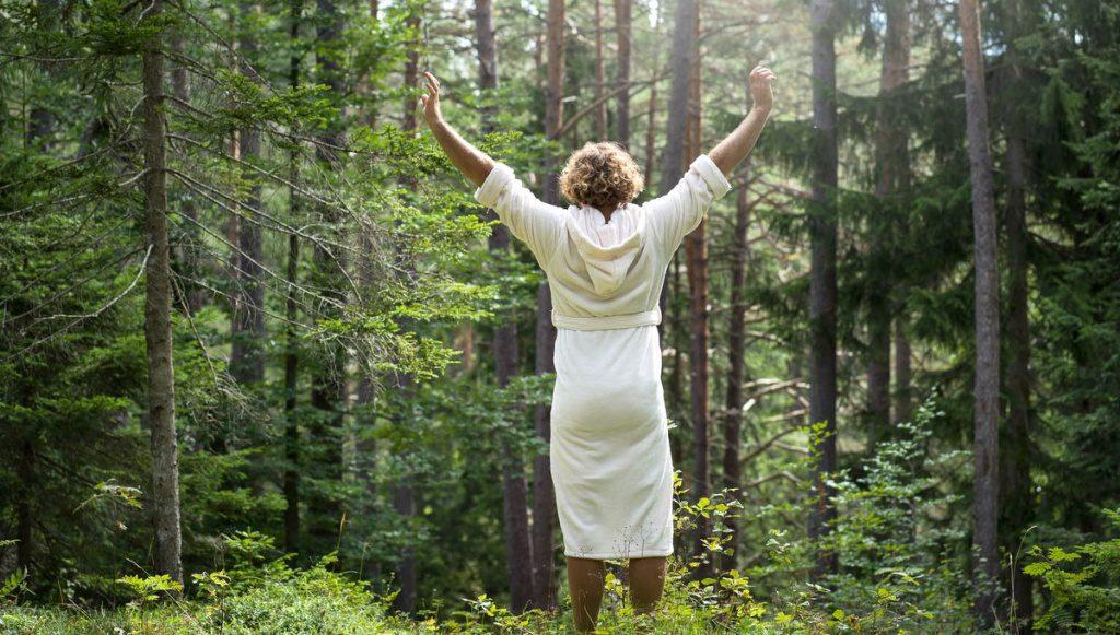 Frau im weißen Bademantel im Wald