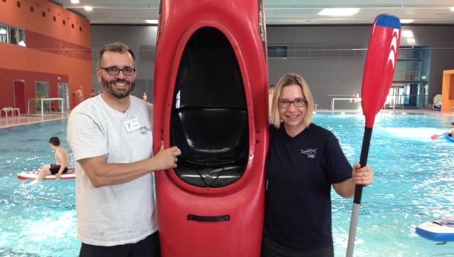 Mann und Frau halten ein Kajak und ein Paddel in einer Schwimhalle