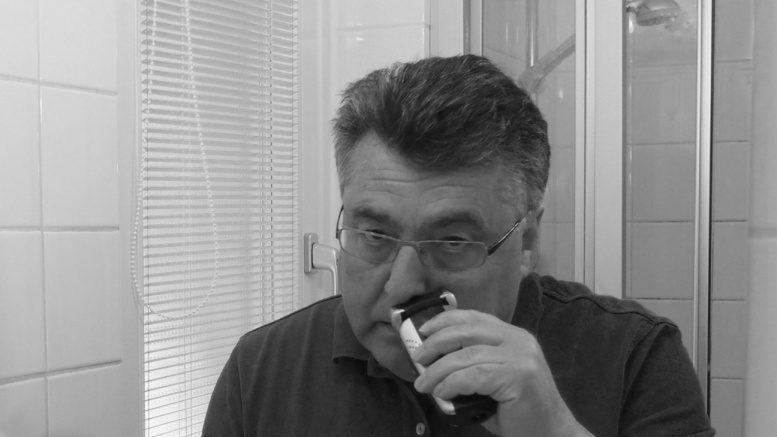 Ein Mann rasiert sich im Bad vor einem Spiegel