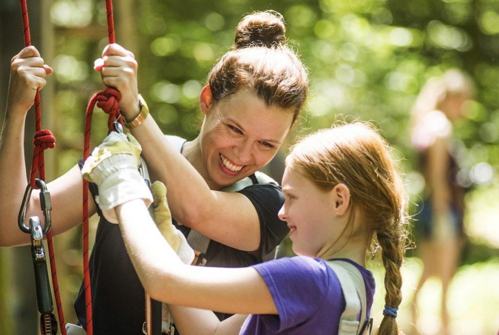 Frau mit Mädchen beim Klettern