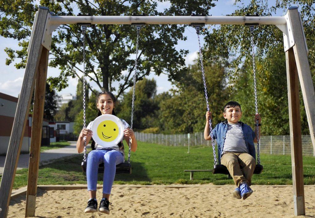Zwei Kinder auf der Schaukel mit Smiley