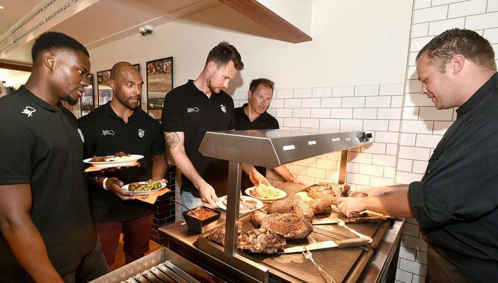 Sportler an der Fleischtheke des Restaurant Flammen