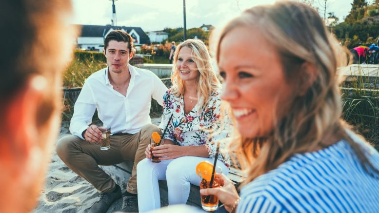 Gruppe von jungen Menschen abends am Strand trinken einen Sundowner