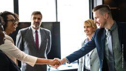 Ein neuer Mitarbeiter wird im Team mit Handschlag begrüßt