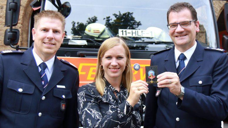 Zwei Feuerwehrmänner mit einer Frau präsentieren einen Charity Pin