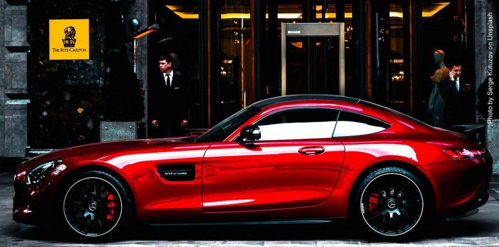 Ein rotes Mercedes Coupe vor einem Luxushotel