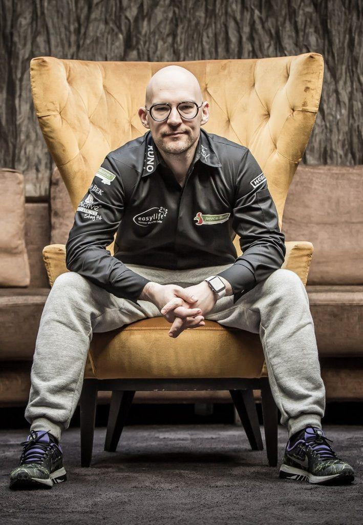 Der TV Koch Benedikt Faust auf einem Sofa