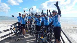 Gruppe von Rennradfahrern zum Abschlußbild auf einer Seebrücke in der Ostsee