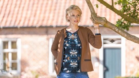 Blonde Frau in einer braunen Jacke