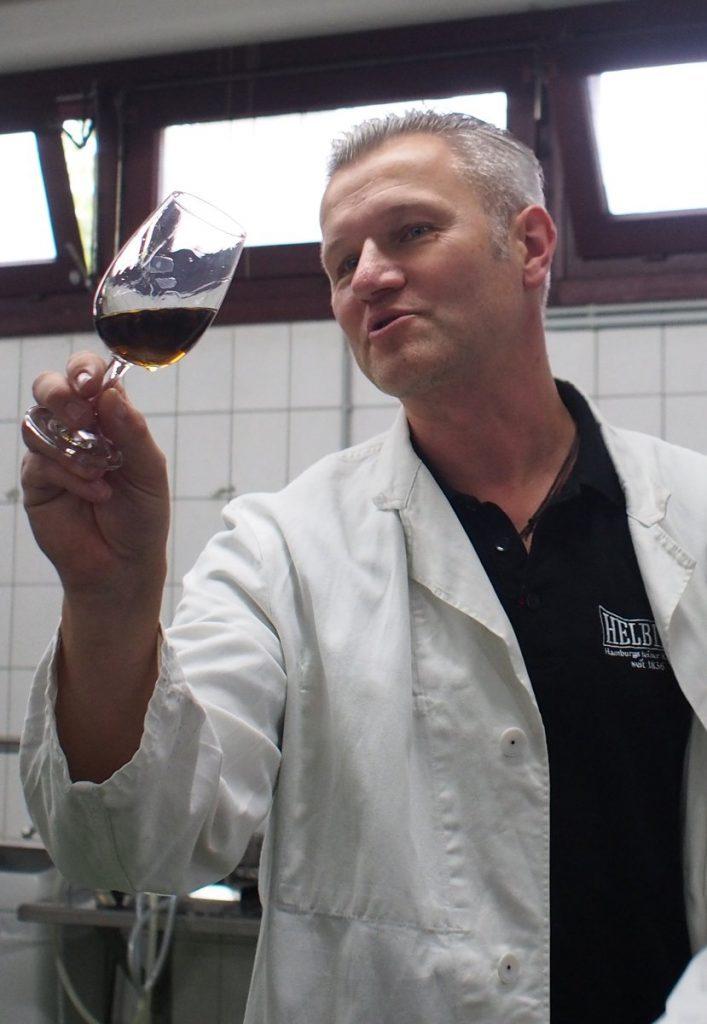 Ein Destilatuer im weißen Kittel prüft die Qualität eines Brandes in einem Glas