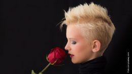 Blonde Frau mit kurzen Haaren riecht an einer roten Rose