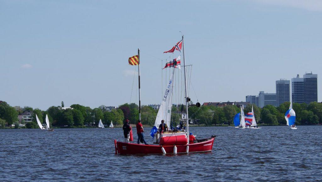 Das rote Leitungsboot des NRV bei einer Regatta auf der Außenalster in Hamburg mit Segelbooten bei gutem Wetter