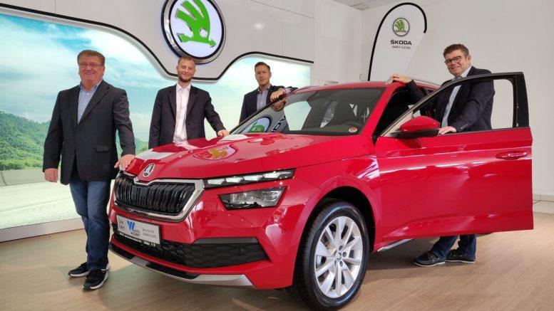 Roter ŠKODA KAMIQ mit Verkäufern von Auto Wichert im Showroom