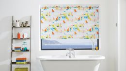 Maritime BadeinrichtungWeiße Badewann mit einem Rollo mit maritimen Motiven