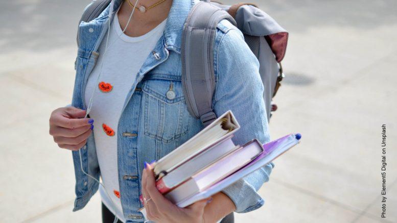 Studentin mit Büchern unter dem Arm